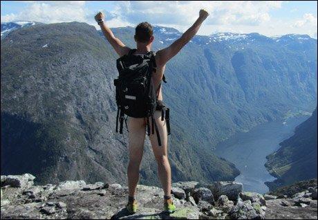 Triumferende mann topper turen fra fjord til fjell.