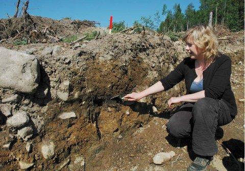 LESER HISTORIEN: I en slik sjakt kan arkeologene ta prøver som forteller om hva jorda er blitt brukt til gjennom århundrene. Her er trekullaget som markerer at skog må ha blitt brent den gang dyrkingen startet, viser feltleder Line Grindkåsa.