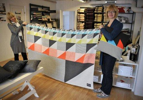 Designer Bente Jørgensen og daglig leder Magnvor Lunåshaug med et av de nyeste pleddene. Det multifargede lammeullspleddet kan brettes på flere måter avhengig av hvilken farge eller hvilket mønster eieren vil vise fram.