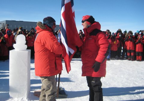 Her overrekker Jens Stoltenberg det norske flagg som en gest til Bill Coughran, direktøren for AmundenScott-basen på Sydpolen.