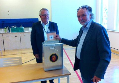 Stein Stensgård legger sin stemme i årets stortingsvalg i urnen. Svein Helgesen i stemmestyret sørger for at alt går riktig for seg.