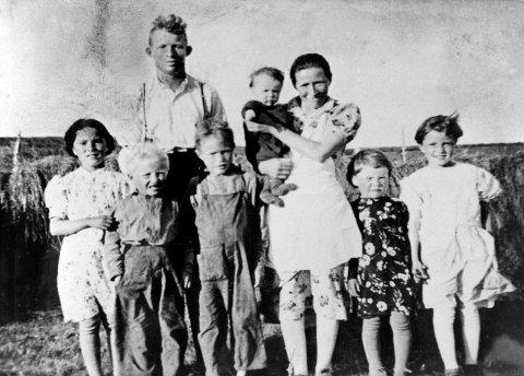 HØYHESJING: Her er familien Andersen samlet før krigen. Alle deltok når høyet skulle på hesjene. Fra venstre Martha Iversen (en nabo), Arne Andersen, far Anders Andersen, Per  Andersen, mor Magga Andersen med datten Signe på armen, Ingrid Andersen (ble gift Dallavara og bor i Vadsø) og Aud Andersen (kusine).