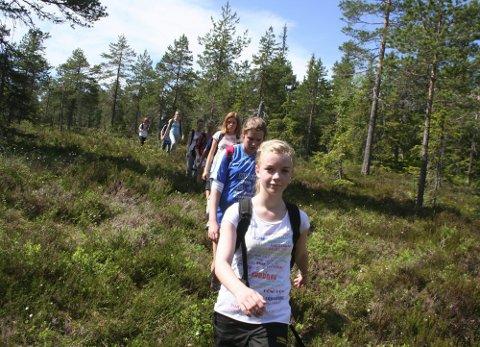 ELEVER PÅ TUR: Elevene fra Runni ungdomsskole tok turen sammen med RB, og ble kjent med kommunens høyeste topp. Her leder Marit Nes Gladeheim an i skogen.