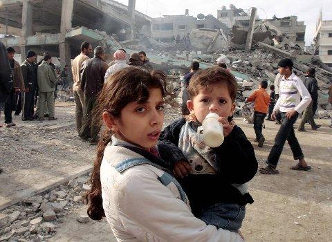 En palestinsk jente bærer sin bror forbi al-Noor moskeen som er fullstendig ødelagt etter israelsk luftangrep i Gaza, 8. januar 2009. I