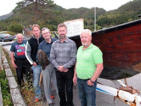Kåre Bøklepp(fra venstre), Tore Sannes, Bernt Bøe, Magnar S. Holten og Inge Dønheim er fem av de som håper at «Hjelmkonnå», søsterskip til «Halsabrura» som de her står ved siden av, snarest flyter på sjøen i Bøfjorden.