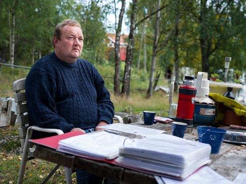 Axel E. Vigdal opplevde at hans 19 sauer ble avlivet på grunn av manglende merking. I forgrunnen har han hele haugen med papirer i saken.