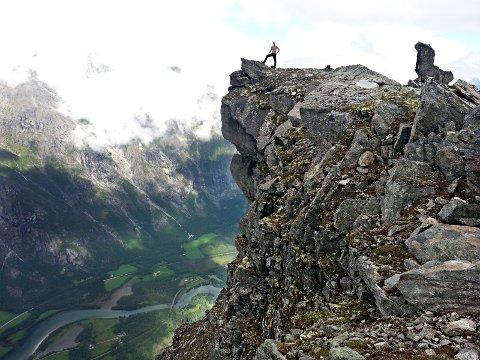 Paul Olav Lyngstad på toppen av Mannen i Rauma. Steinmannen som har gitt fjellet navn ser vi helt til høyre.