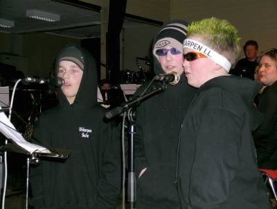 Det er ikke hverdagskost med korpsmusikk med rap. Her ser vi Simon Stenhaug, Victoria Fenes og Kristoffer Almli synge rap med korpset. Foto: Elin Rønning