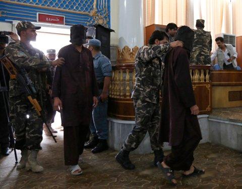 To av de sju mennene som søndag ble dømt til døden for voldtekt og ran, føres inn i rettssalen i Kabu.