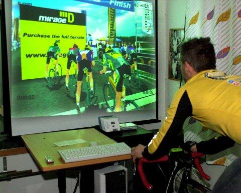 SYKKELRITT PÅ SKJERM: Terrengsykling kan faktisk foregå innendørs hvis man bruker digitalt utstyr til hjelp. Tom Eriksen kjører sykkelritt hjemme i kjellerstua med motstandere på storskjerm. (Foto: Per Vikan)