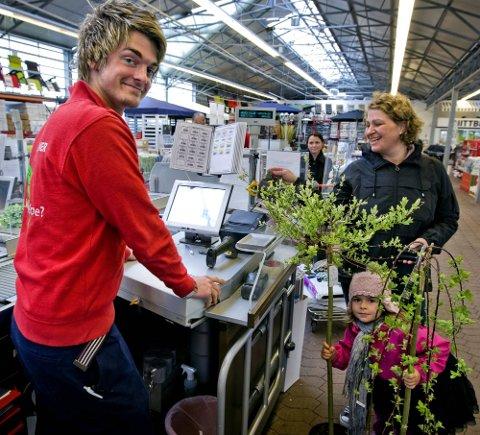 JA: Robin Holøien jobber hos Plantasjen i Sarpsborg Han synes det er helt greit å jobbe på søndager, så lenge han får godt betalt. Han er godt fornøyd med søndagstillegget. Her betjener han kundene Hanne Kvam og Anna Hannesdatter Kvam.