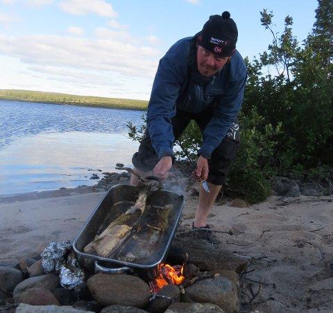 «KRINGLER-KOKKEN»: Thomas Pedersen er en magiker med Lake Trouten! Her jobber han med nydorget fisk fra siste etappe før lunsj. Peter trakk et par stykker på jamt over kiloen ? og det ble kongelig lunsj på bredden av Sandy Lake.