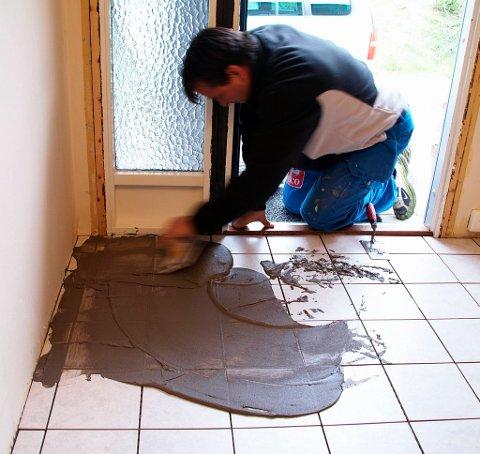 Arbeid fugemassen utover gulvet med en sparkel.