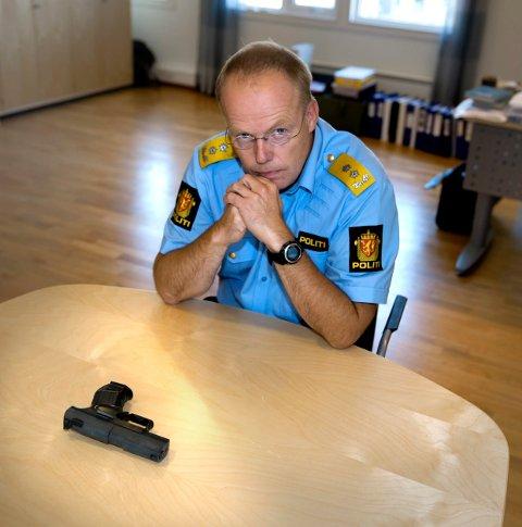 ADVARER: Du kan risikere å bli skutt hvis du truer med en våpenetterlikning, sier politimester Johan  Mrtin Welhaven. På bordet foran ham ligger en etterlikning av en pistol benyttet i James Bond-filmer. Våpenet er tidligere beslaglagt av politiet.