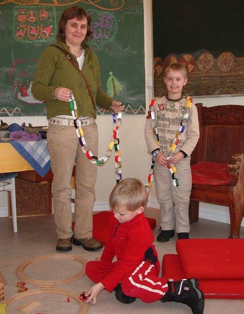JULETRELENKE: Mamma Lene og sønnen Nicolai Drager hadde laget en lang juletrelenke. Even Pedersen var mest opptatt av togbanen.Bestill bilde