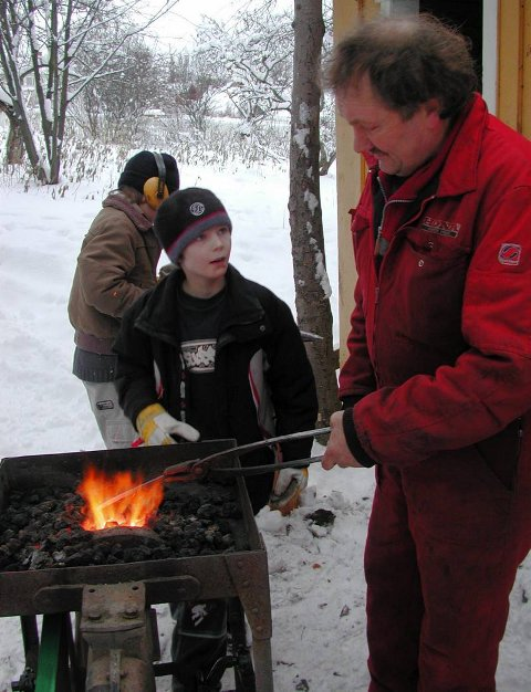 SMIE: 5. klassingen Amund Hasle får hjelp til å smi en lysestake av Odd Kleven. Først må metallet varmes.Bestill bilde