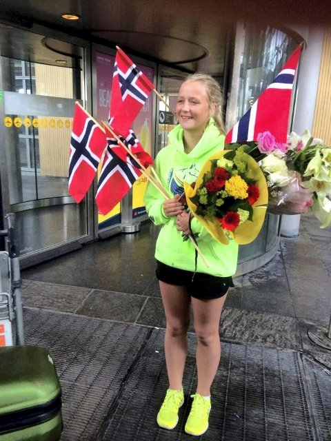 feiret: Miriam Sandvik og gullmedaljen ble møtt av norske flagg og blomster på Gardermoen.foto: privat