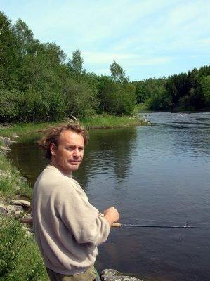 ÅGÅRDSELVA: Her prøver Harald Beyer-Olsen fiskelykken i Ågårdselva. Så langt har han ikke hatt napp, men han forsikret at det er fin rekreasjon å være ved elva. (Foto: Ingrid Aune)