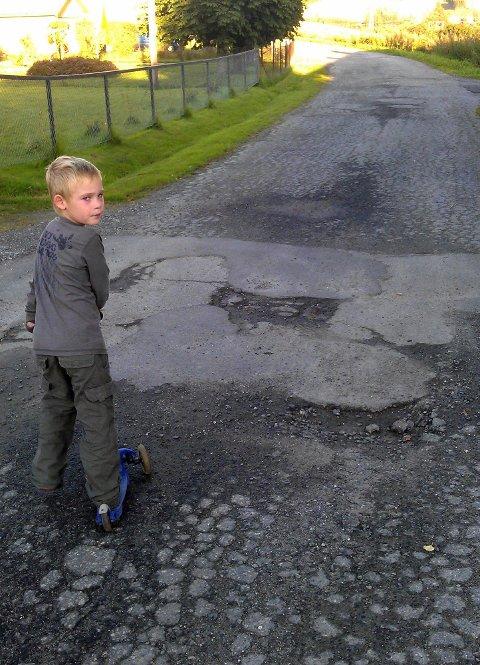 MISFORNØYD: Leo Fosshaug (5) liker dårlig at veien i nabolaget er så hullete. BEGGE FOTO: Espen Fosshaug