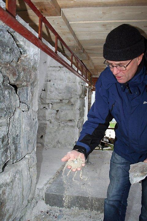 NØDVENDIG: Kirkeverge Bjørnar Torgersen viser hvordan sementlaget mellom steinblokkene på Brønnøy Kirke smuldrer mellom fingrene hans. Behovet for renovering av veggene var stor.