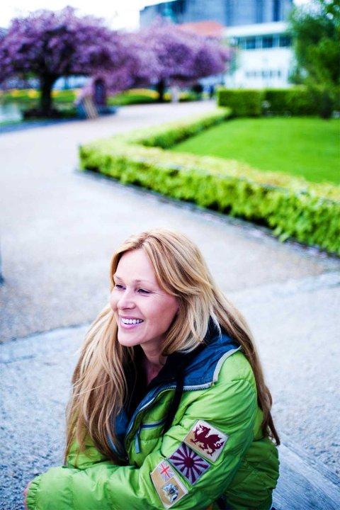 """Dorthe Skappel på plass i Bergen, med Grieghallen i bakgrunnen. Bak ser man også de japanske kirsebærtrærne som har inspirert """"Gullruten""""-showet."""