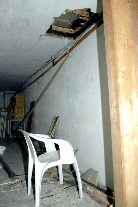 TUNG JOBB: Innbruddstyven(e) har stått på en campingstol i kjelleren mens de saget seg gjennom gulvet.