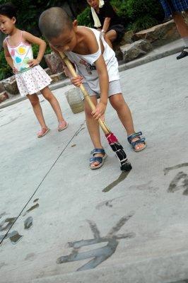 BASIC CHINESE: En liten gutt i Heping Park, Shanghai, imponerer far og bestefar og forbipasserende med sine skriveferdigheter, demonstrert på parkalleens asfalt med våt «penn». Det kinesiske alfabet har rundt 60 000 tegn og man må kunne 3000 for å lese en vanlig avis.