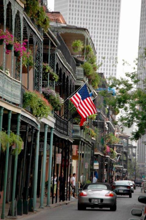 Det amerikanske flagget vaier friskt i vinden på smijernsbalkongene i det franske kvarteret.