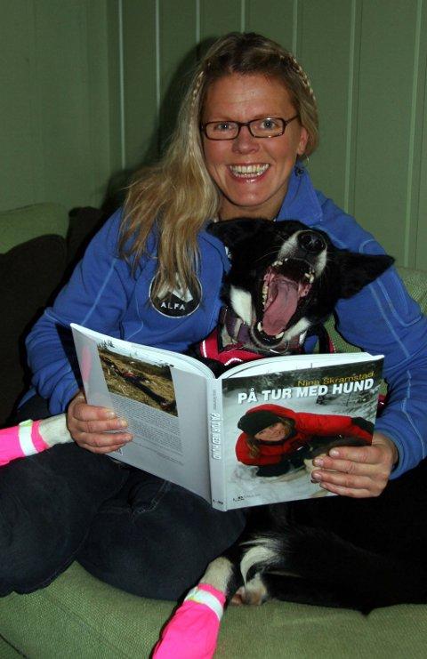 Med rosa sokker og sele: Dette er et smil, ikke et gjesp, formidler Delta, fornøyd med høytlesingen fra boka «På tur med hund» på matmor Nina Skramstads fang.
