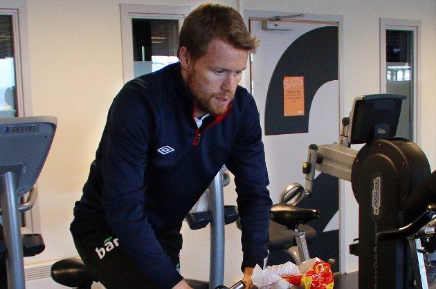 Tom Høgli på sykkelsetet på SATS Langnes i Tromsø, der han trener seg opp mot landskampen mot Bulgaria.