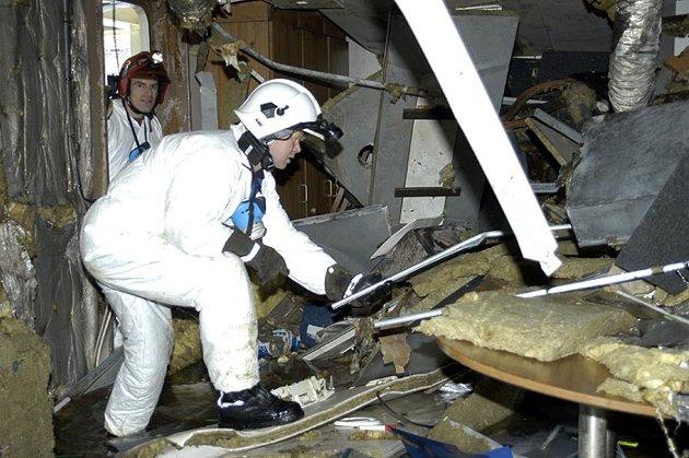 """Frank Åstveit (fremme) og Ronny Sandanger undersøker en av lugarene på """"Rocknes"""" etter at skipet ble snudd ved CCB-basen på Ågotnes i mars 2004."""