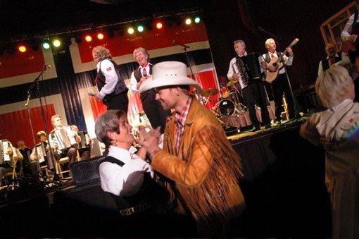 SVING: I front er det neste band på scenen, norske Kentucky Riders, som varmer opp til eget show ved svinge seg med en av bunadsdanserne fra Lindesnes-klubben.