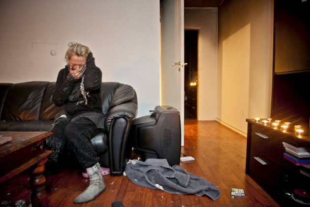 Gunn-Elin har tent stearinlys, i den mørke stuen. Hele leiligheten, bortsett fra kjøkkenet, er mørklagt.