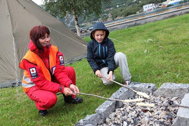Liv Wenche Dyrstad i Svelgen Røde Kors og Lukas Dyrstad (10) grillar pinnebrød.