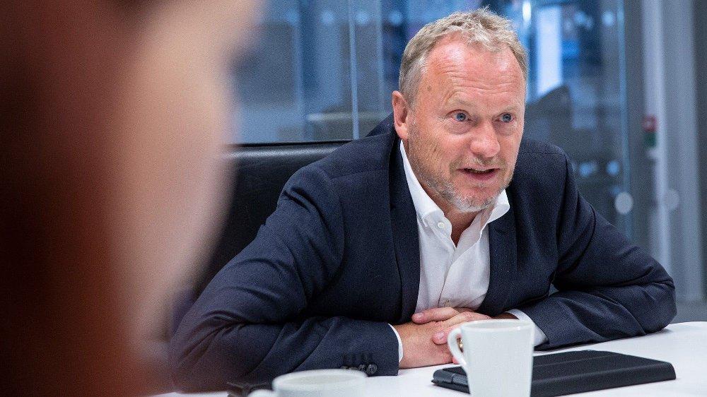 Klikk på bildet for å forstørre. Raymond Johansen sitter ved et bord og lener seg fremover.