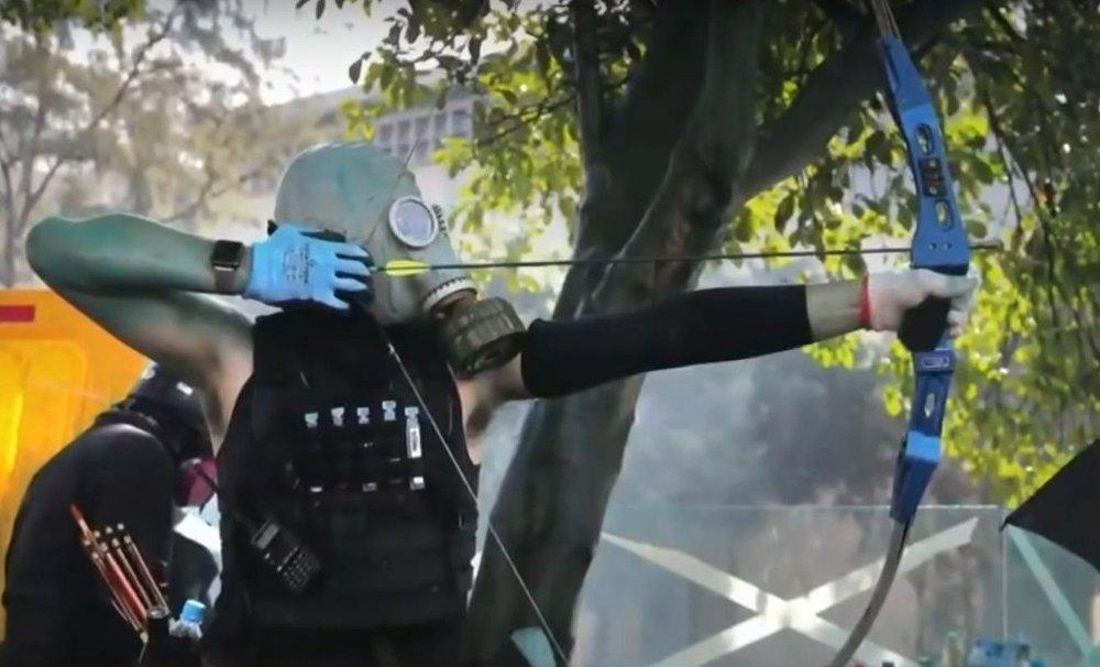Klikk på bildet for å forstørre. En demonstrant i aksjon med pil og bue i Hongkong søndag 17.11.19.