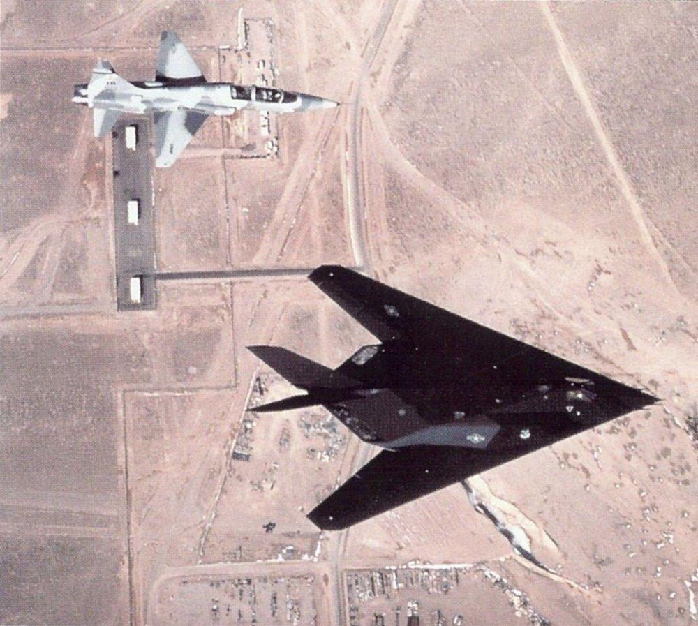 Klikk på bildet for å forstørre. An F-117 Nighthawk with a T-38 Talon chase plane flying over Tonopah Test Range Airport.