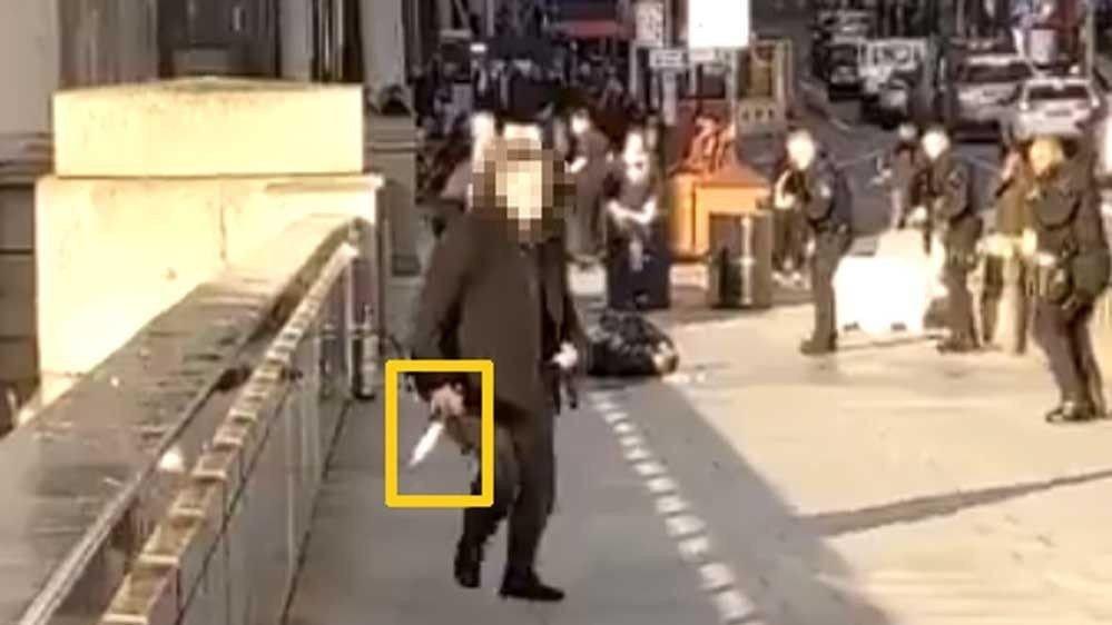 Klikk på bildet for å forstørre. På en av videoene som er lagt ut på Twitter kan man se denne mannen som har det som ser ut som en kniv i hånden, løpet fra stedet etter at en person blir skutt. Det er uklart hvorfor mannen har en kniv i hånden, men det kan se ut som han har har vært med å å hjelpe politiet med å overbemanne gjerningspersonen, og tatt fra vedkommende kniven. Mannen med kniven ber også folk på broen om å løpe vekk fra stedet.