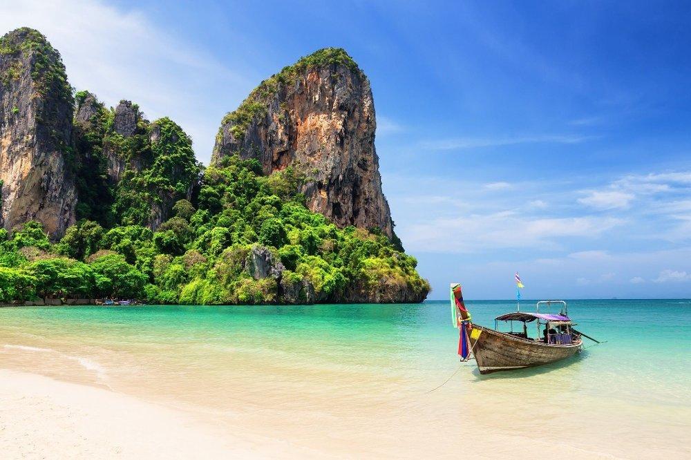 Klikk på bildet for å forstørre. Thai traditional wooden longtail boat and beautiful sand beach Thai traditional wooden longtail boat and beautiful sand Railay Beach in Krabi province. Ao Nang, Thailand.