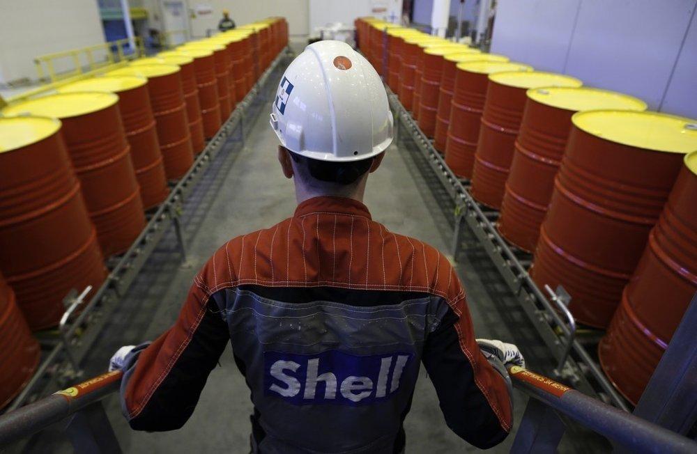 Klikk på bildet for å forstørre. Illustrasjonsfoto: En ansatt i Royal Dutch Shell står foran en rekke oljetønner på selskapets fabrikk i Torzhok i Russland.