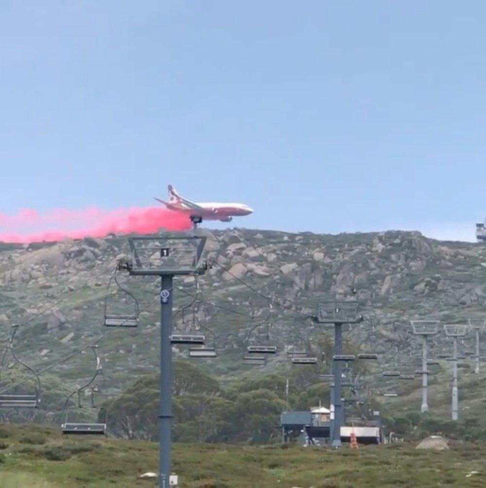 Klikk på bildet for å forstørre. Et fly slipper ut pulver for å hindre spredning av skogbrannen i Snowy Mountains i New South Wales mandag.