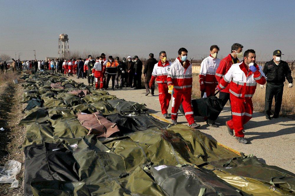 Klikk på bildet for å forstørre. Iranske redningsmannskaper håndterer de omkomne etter flystyrten i Iran onsdag.