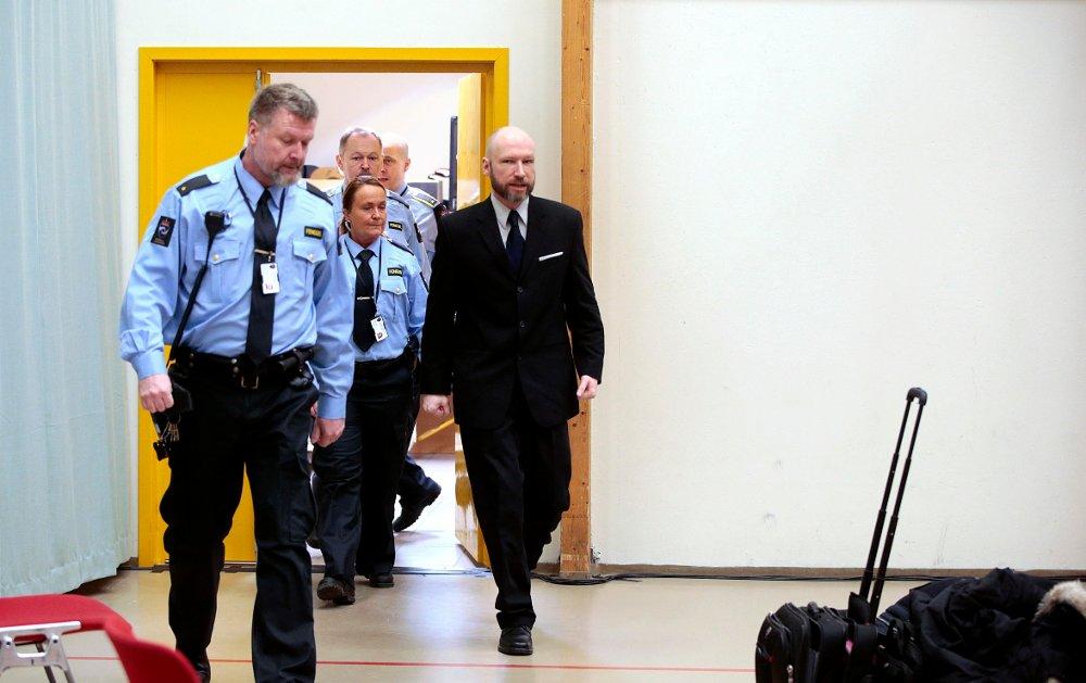 Klikk på bildet for å forstørre. Anders Behring Breivik ankommer rettssalen omringet av fengselsbetjenter.