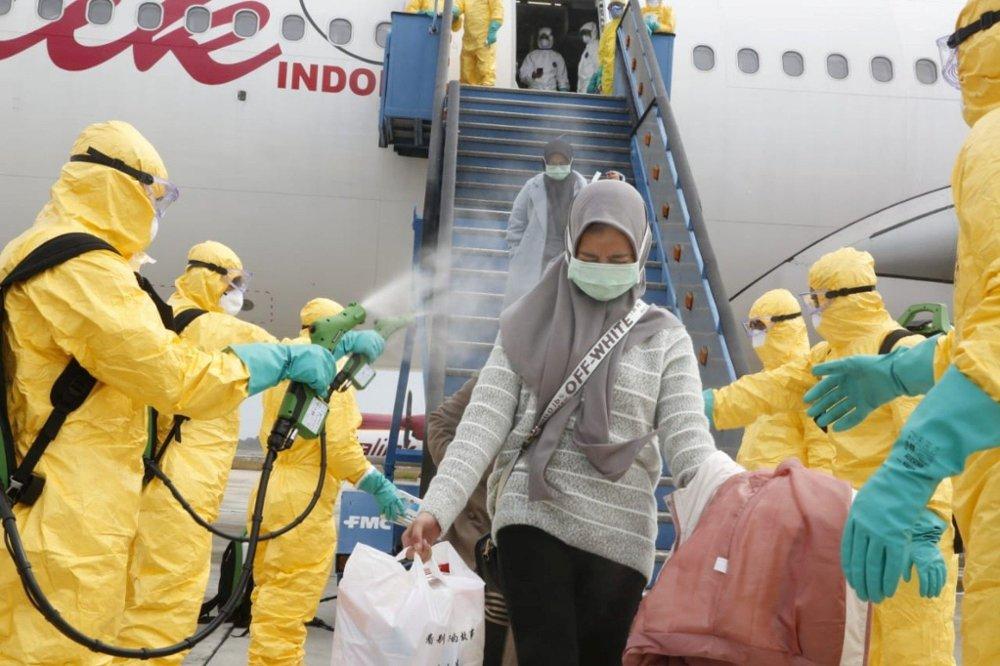 Klikk på bildet for å forstørre. Kina er ikke alene om å ta forholdsregler. Indonesisk helsepersonell sprayer med desinfiserende middel på passasjerer som ankommer fra den kinesiske byen Wuhan.