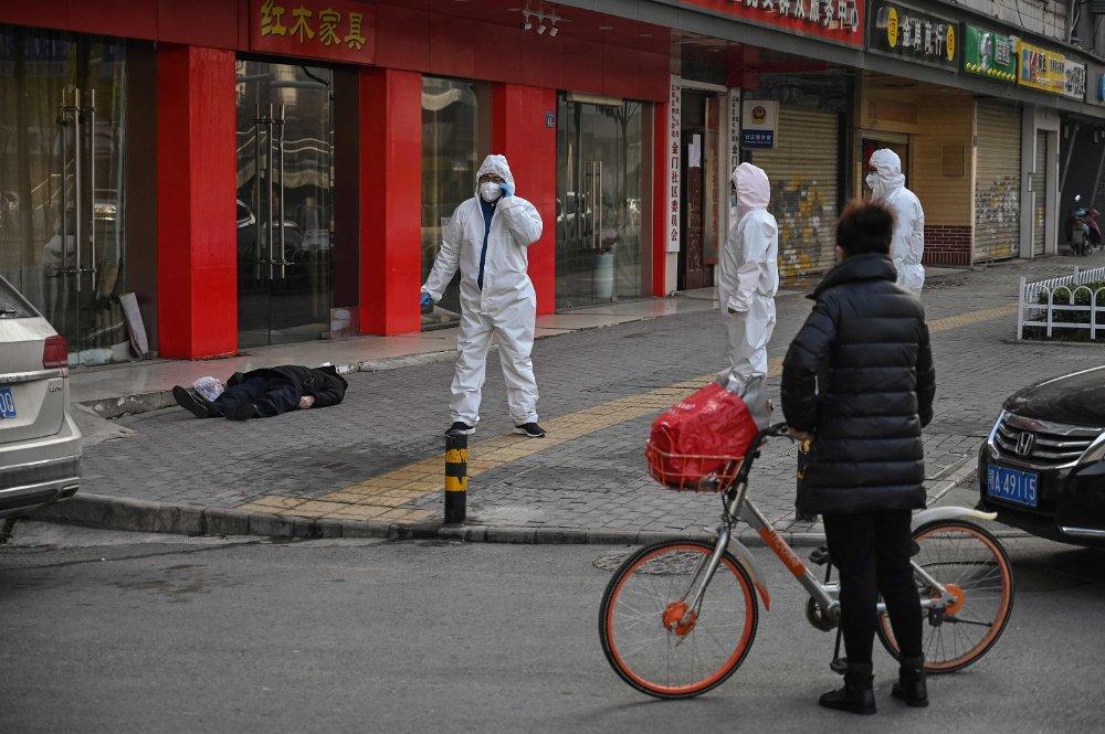 Klikk på bildet for å forstørre. En eldre mann falt om og døde på et fortau i byen Wuhan for to uker siden. Helsepersonell tar ingen risiko.