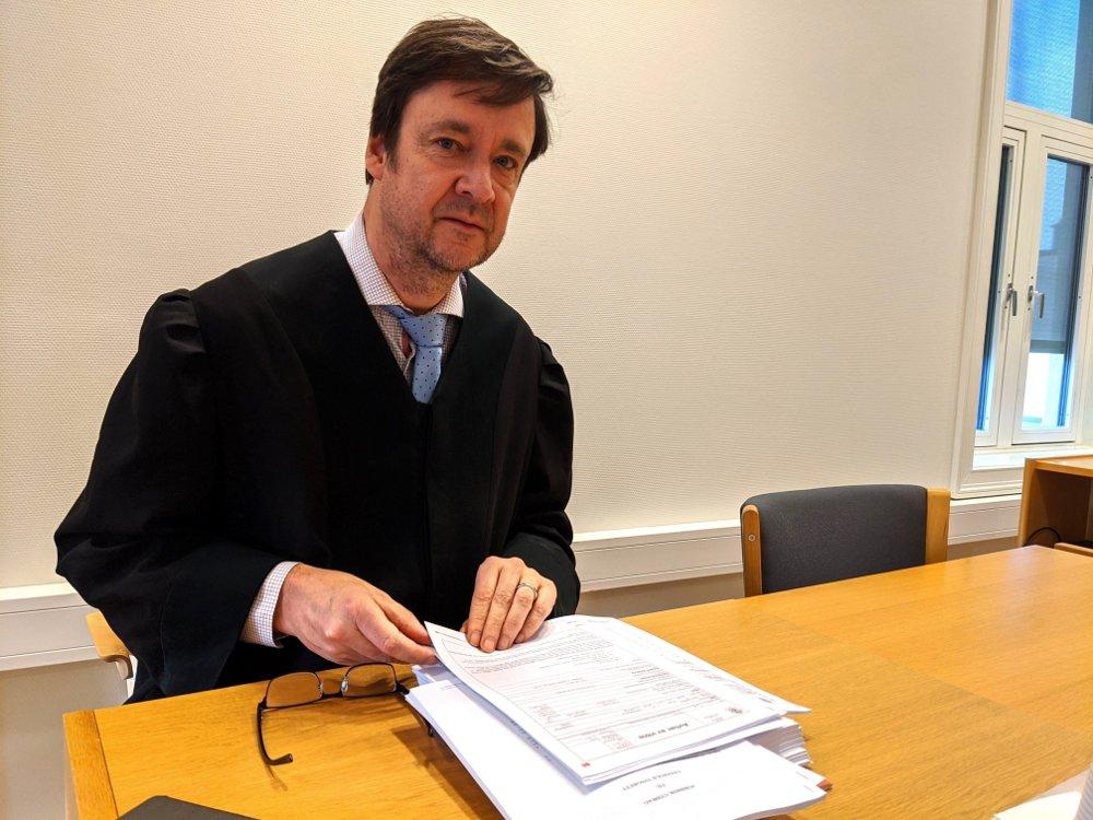 Klikk på bildet for å forstørre. John Christian Elden sitter ved pulten sin i tinghuset i Larvik. Ser i kamera. Har på seg advokatkappe.