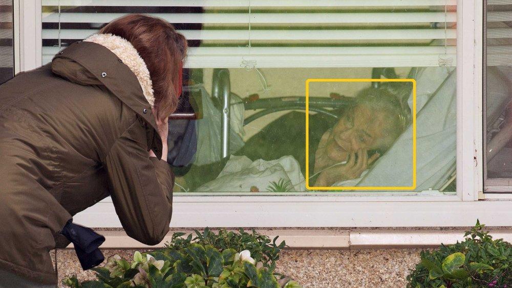 Klikk på bildet for å forstørre. På bildet kan du se Lori Spencer som snakker på telefonen gjennom et vindu med moren, Judie Shape , som nå blir testet for coronaviruset. Judie Shape er beboer ved Life Care Center of Kirkland.