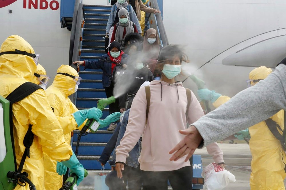 Klikk på bildet for å forstørre. Indonesiere blir desinfisert idet de kommer hjem fra Wuhan i Kina.
