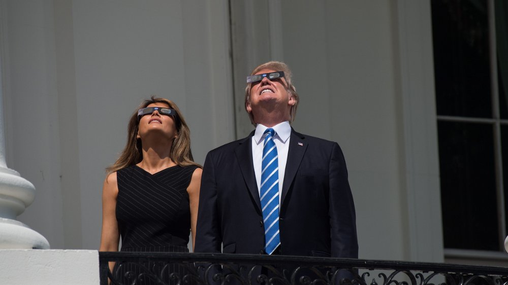 Klikk på bildet for å forstørre. US President Donald Trump looks up a the partial solar eclipse with First Lady Melania Trump from the balcony of the White House in Washington, DC, on August 21, 2017. The Great American Eclipse completed its journey across the United States Monday, with the path of totality stretching coast-to-coast for the first time in nearly a century. / AFP PHOTO / NICHOLAS KAMM