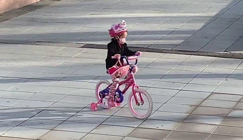 Klikk på bildet for å forstørre. Denne lille jenta sykler rundt i den lille parken, Court Square Park, med en matchende ansiktsmaske.